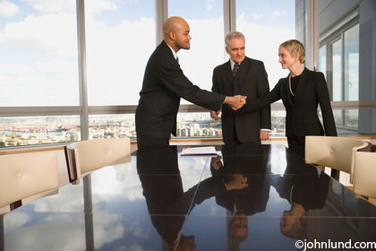 Picture of a group of three businesspeople standing at a conference table in a conference room shaking hands and smiling.